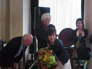 ④ 室内でのトーク後は、一緒におもてなしくださった北原先生の奥様 旬子夫人に。 協会から感謝の花束。プレゼンターは協会副会長河合先生。